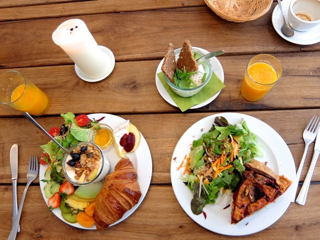 left: Französisches Frühstück (croissant, warm camembert, jams, orange quark with granola) salad, top: two poached eggs with arugula in a glas, right: red beet carrot quiche with salad