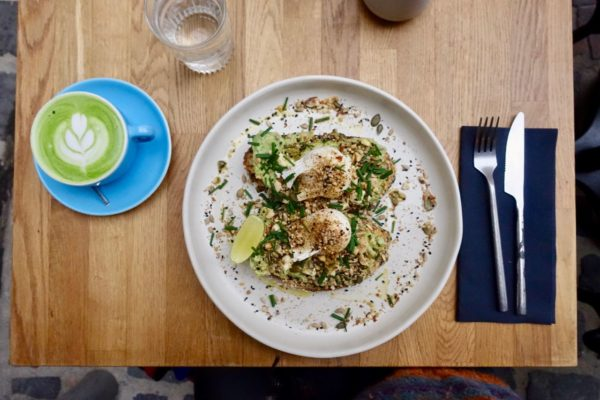 matcha latte and avocado toast with feta, dukkah, poached eggs, lime, sprouts and seeds